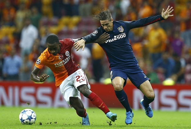 Atletico Madrid's Torres fights for the ball with Galatasaray's Carole during their Champions League Group C soccer match in Istanbul